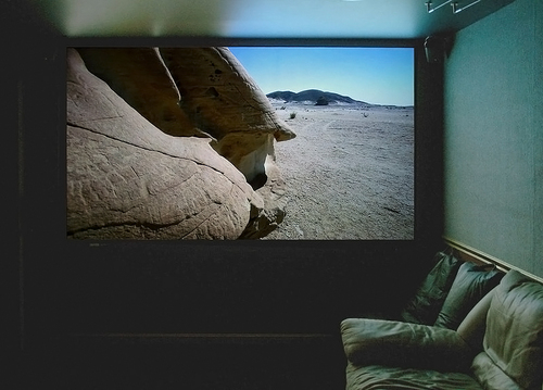 A large projection screen in a media room by Wikimedia Commons